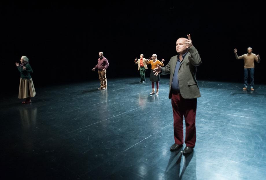 Ausgangsformation für die Wiederholungen in 10xTheEternal: fünf Menschen stehen in einer Position auf der Bühne, die von oben betrachtet an einen Würfel mit der Zahl fünf erinnert.