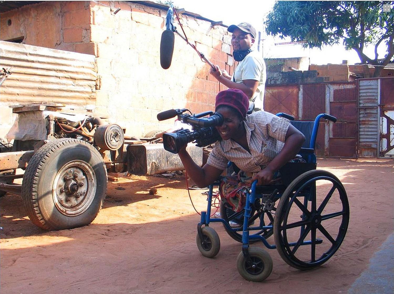 Ein Mann im Rollstuhl filmt mit einer Kamera, über ihm hängt ein Mikrophon