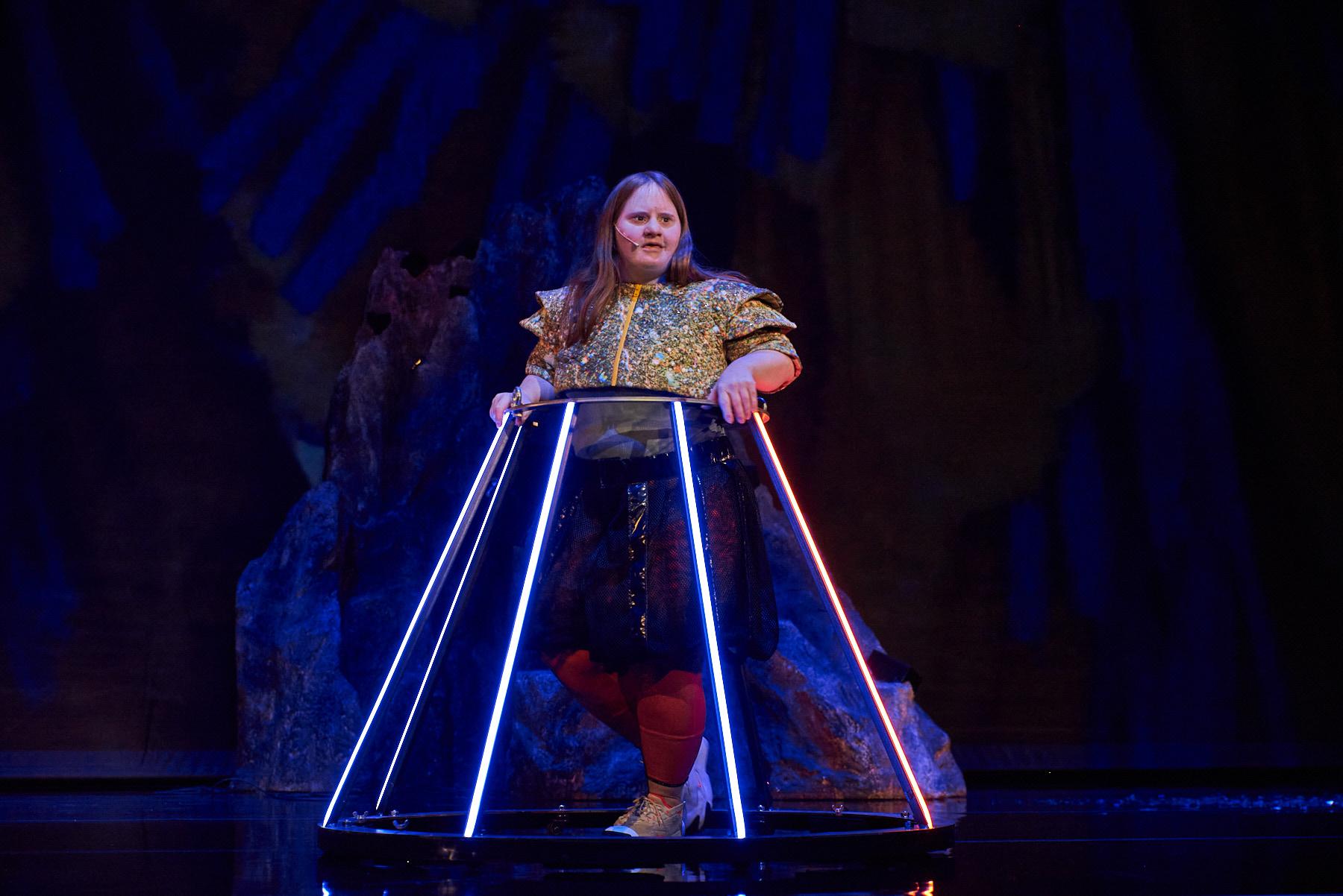 Julia Häusermann steht auf einer dunklen Bühne. Sie trägt ein buntes Outfit. Um sie herum ist ein Konstrukt mit Leuchtstäben, welches eine Art Reifrock darstellen könnte