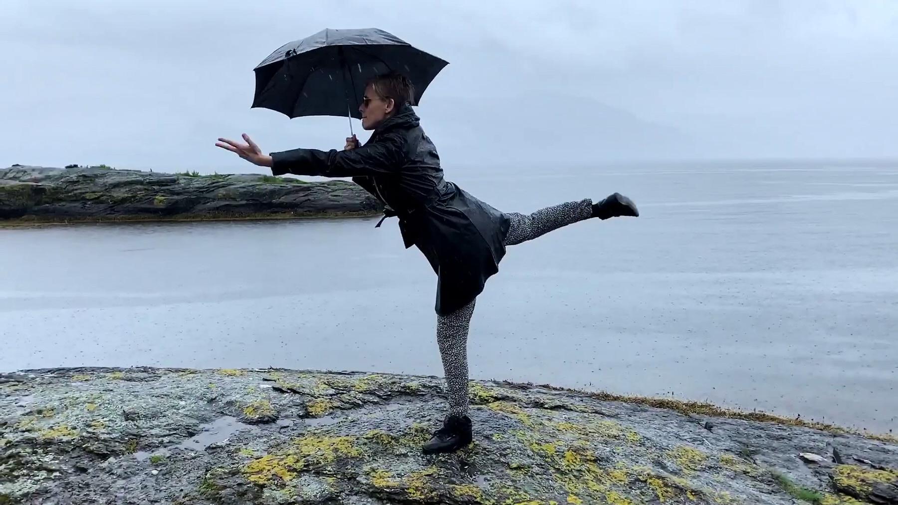 Frau in schwarzer Kleidung und mit Regenschirm tanzt am Meer