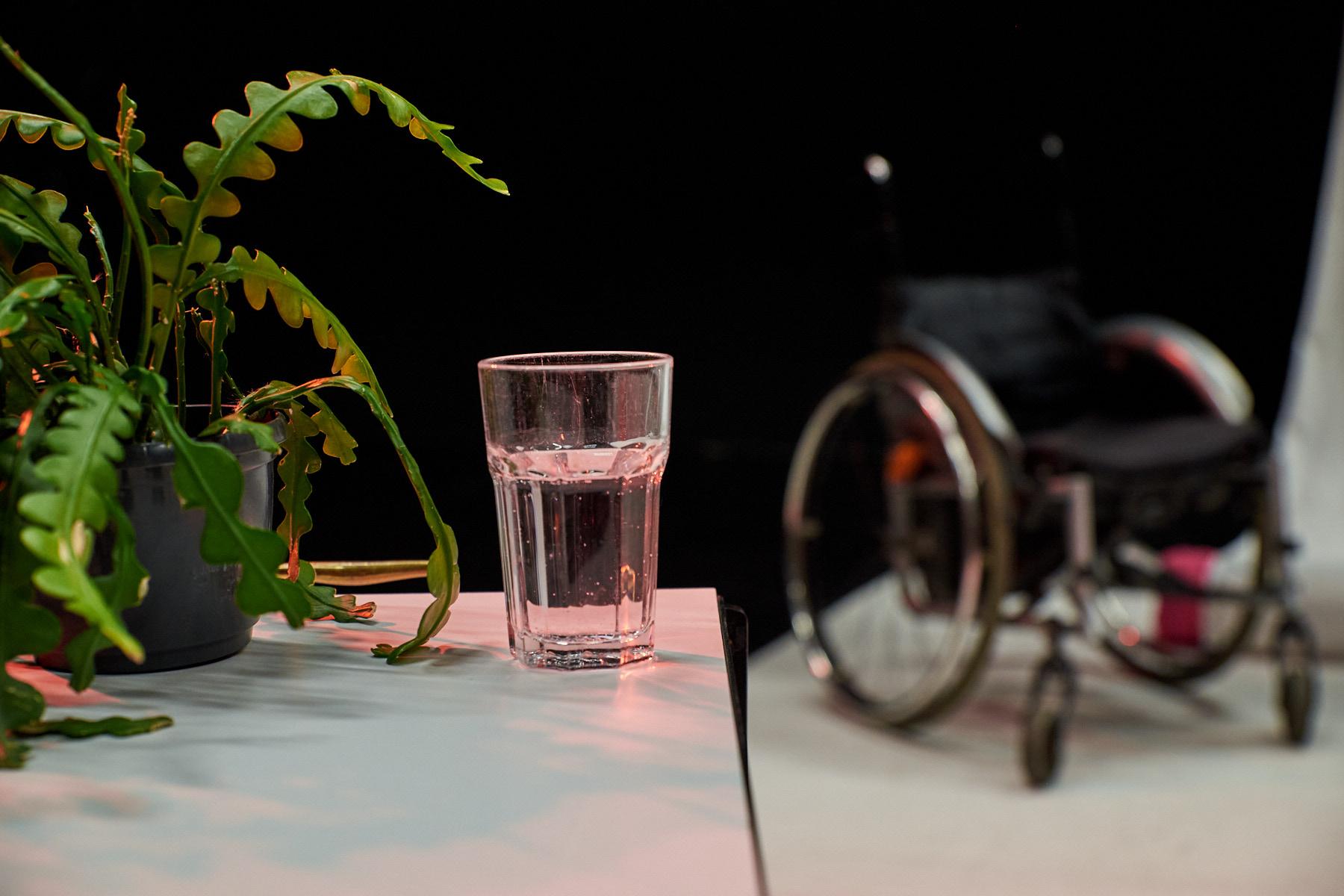 Ein Glas Tonic Water neben Topffplanze mit Rollstuhl im Hintergrund