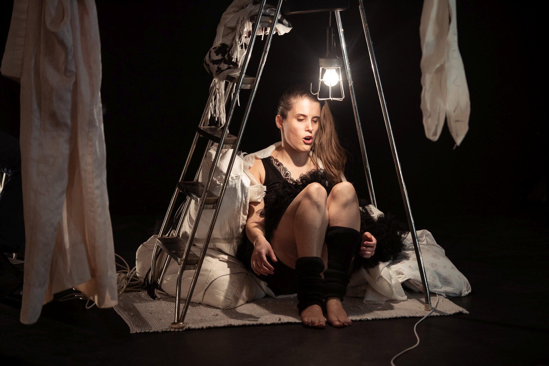 Eine junge Frau mit langen braunen, zum Zopf gebundenen Haaren sitzt unter einer aufgeklappten Leiter. Über ihrem Kopf hängt eine leuchtende Glühbirne. Sie sitzt auf einem kleinen Teppich, auf dem auch Kissen liegen. Um sie herum ist es dunkel. Die Lampe ist die einzige Lichtquelle.